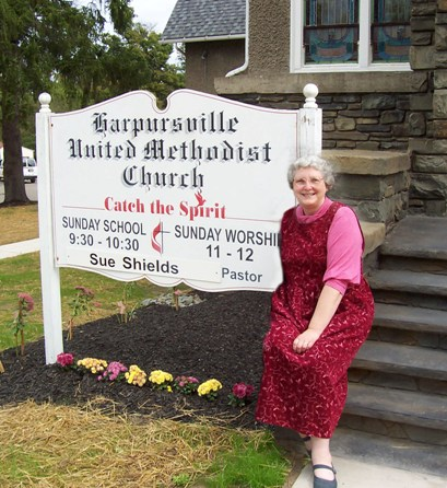 Photo of Linda Bonney Olin sitting on steps of Harpursville United Methodist Church